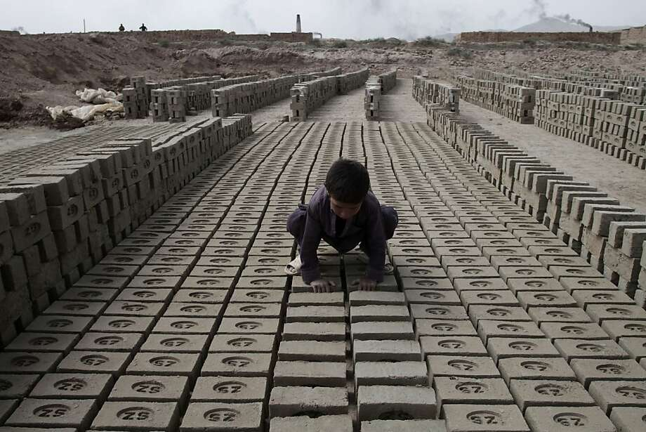 Minimal wage:An Afghan boy arranges bricks at the brick factory where his father works on the   outskirts of Kabul. Laborers earn $12 dollars a day per 14-hour shift, six days a   week. Photo: Rahmat Gul, Associated Press