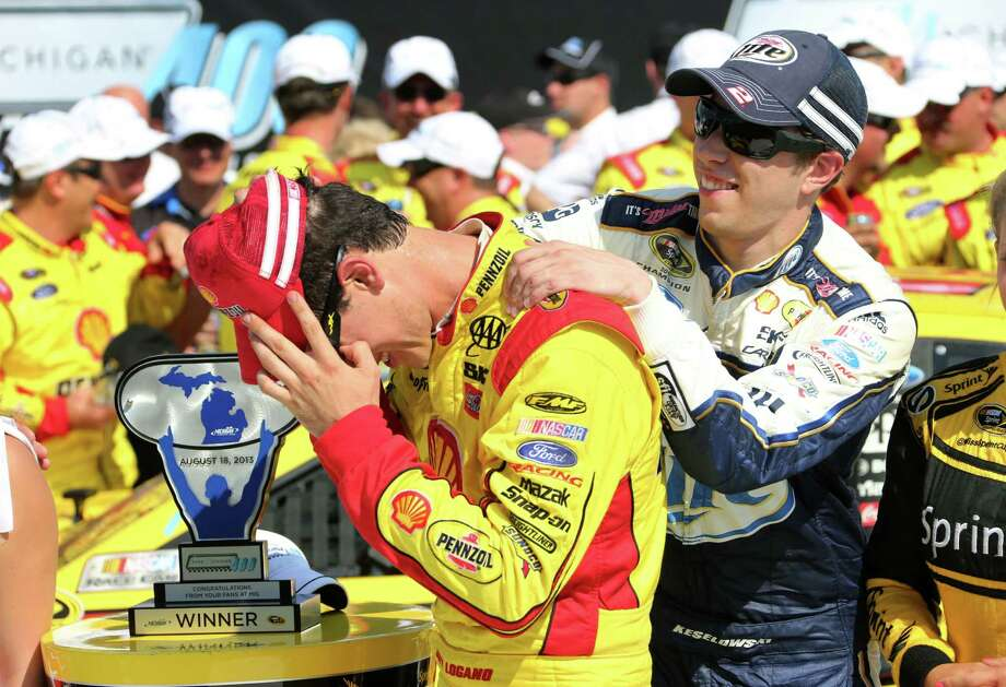 Brad Keselowski (right) congratulates Joey Logano after his Penske Racing teammate won the Sprint Cup race at Michigan International Speedway. Photo: Bob Brodbeck / Associated Press