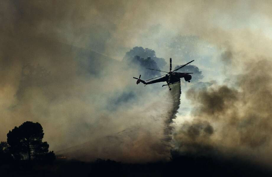 A fire helicopter dumps water on a brush fire near Highway 101 and Calabasas on August 18, 2013 north of Los Angeles, California.  A car fire sparked a brush fire off the northbound 101 Freeway in Calabasas on Sunday.  LA County Fire says the blaze has burned between 40 to 50 acres. Crews are battling flames from the ground and air.    AFP PHOTO / JOE KLAMARJOE KLAMAR/AFP/Getty Images Photo: Joe Klamar, AFP/Getty Images