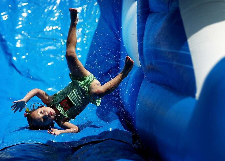 Kitara Acker, 3, flips upside down as she slides on an inflatable water slide during the Back to School Splash Bash at Christ the King Lutheran Church and School Sunday Aug. 18, 2013. The church had several inflatable slides and well as kiddie pools and free hot dogs to celebrate the children's return to school and mark the beginning of the new Sunday School year. (AP Photo/The Commercial Appeal, Mike Brown) Photo: Mike Brown, Associated Press