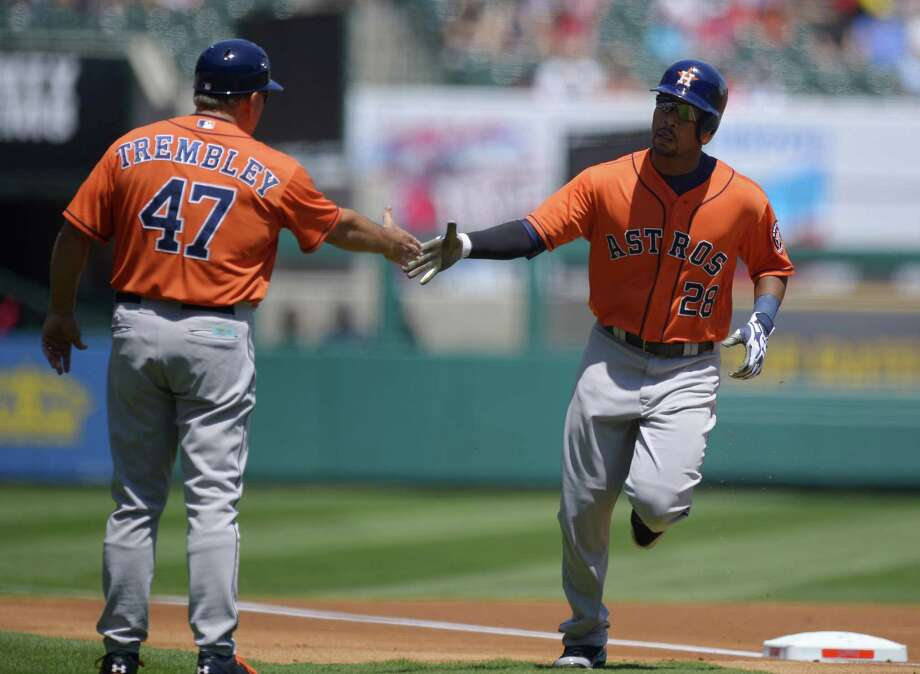 The Astros' L.J. Hoes is congratulated by third-base coach Dave Trembley after hitting his first career big-league home run Sunday in Anaheim, Calif. Photo: Mark J. Terrill / Associated Press
