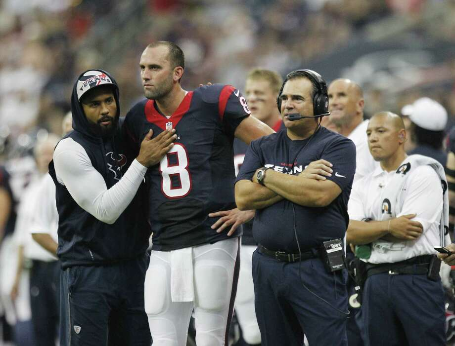 Texans running back Arian Foster (left), who hasn't suited up in the preseason because of a back injury, offers some support to QB Matt Schaub in Saturday's 24-17 win over the Dolphins. Photo: Brett Coomer / Houston Chronicle