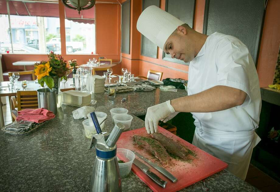 Chef Manny Torres Gimenez seasons a steak at The Palace. Photo: John Storey, Special To The Chronicle