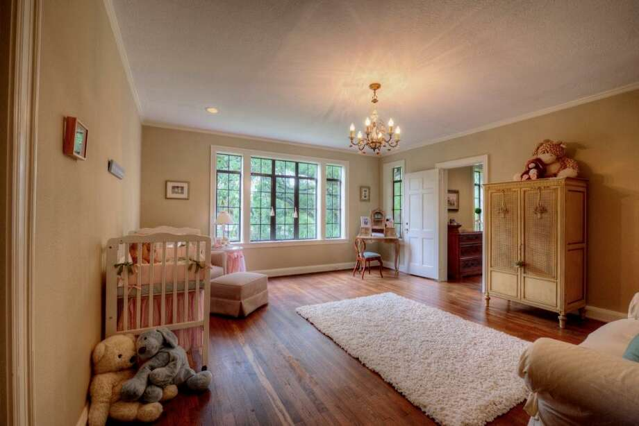 This charming secondary bedroom, 17' x 15', is located off of the hallway, closest to the master suite. Currently used as a sitting room with nursery, the room's view take on a tree-house effect looking out upon the expansive yard.See the listing here.
