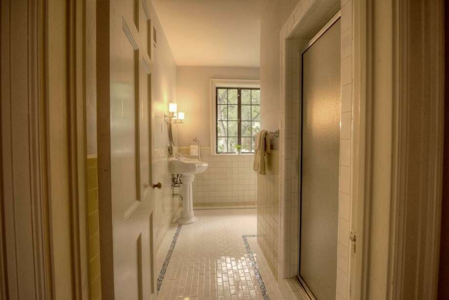 "Also renovated in 2013, this bathroom incorporates a walk-in shower, with the new commode tucked away around the corner. The 2"" x 4"" tile, with glass mosaic 'rug', help to complement the column-style pedestal and new faucet.See the listing here."