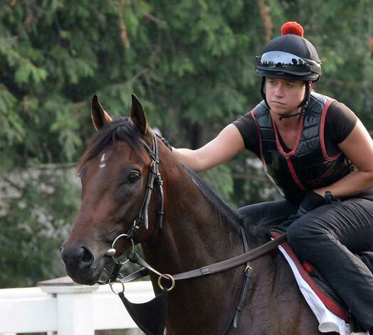 Exercise rider Jen Patterson gives Kentucky Derby winner Orb some affection Monday morning, Aug 19, 2013, before his final major work on the Oklahoma Training Center track in Saratoga Springs, N.Y.  Orb will compete in Saturday's Travers Stakes at Saratoga Race Course.  (Skip Dickstein/Times Union) Photo: SKIP DICKSTEIN