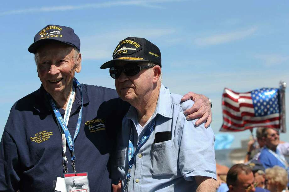 World War II veterans Ed Coyne, left, of Texas, and Thomas Dugan, of South Carolina, embrace after meeting during a ceremony at the Intrepid Sea, Air & Space Museum marking the 70th anniversary of the ship's commissioning Friday, Aug. 16, 2013 in New York. Coyne and Dugan served together on the Intrepid when it was first commisioned.  (AP Photo/Mary Altaffer) ORG XMIT: NYMA101 Photo: Mary Altaffer, AP / AP