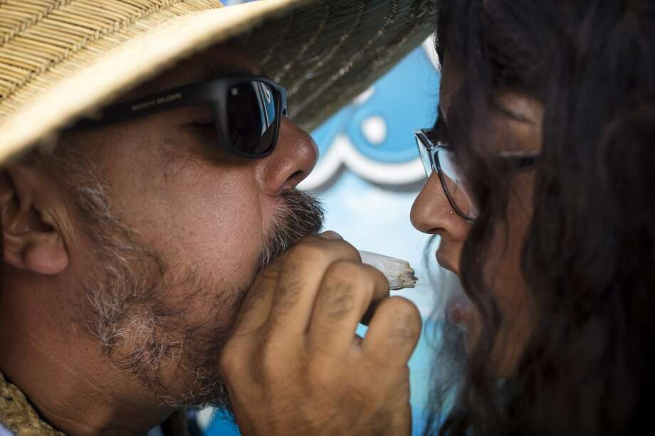 Paradise Vape employees Tio Cervantes, left, blows smoke through his 10-gram blunt into the mouth of Chayse Salvini, right, on the third and final day of Seattle Hempfest Sunday, August 18, 2013, at Myrtle Edwards Park in Seattle. (Jordan Stead, seattlepi.com)2 Photo: JORDAN STEAD, SEATTLEPI.COM