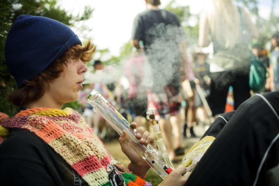 Smoking from under his quilt-meets-bib, Gosh Wilson enjoys a moment of peace on the side of a busy walkway on the third and final day of Seattle Hempfest Sunday, August 18, 2013, at Myrtle Edwards Park in Seattle. (Jordan Stead, seattlepi.com) Photo: JORDAN STEAD, SEATTLEPI.COM