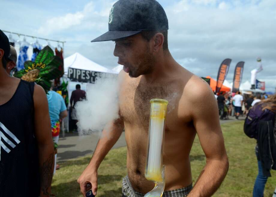 A man smokes a bong on the second day of Seattle Hempfest Saturday, Aug. 17, 2013, at Myrtle Edwards Park in Seattle. This is the first year for the annual pro-pot rally since Washington State voters legalized recreational use of marijuana. (Sy Bean, seattlepi.com) Photo: SY BEAN, SEATTLEPI.COM