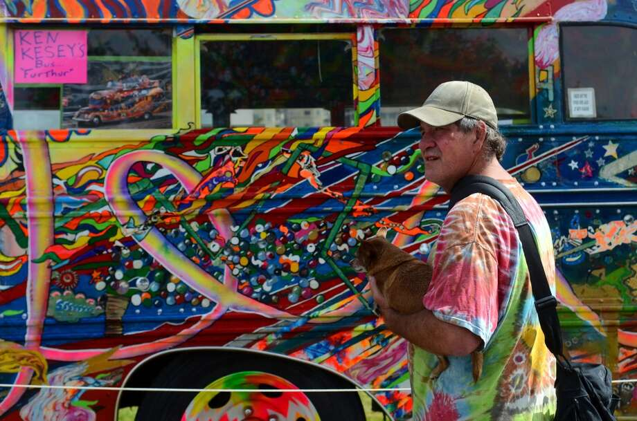 An attendee stands in front of Ken Kesey's bus, the Further, during the second day of the annual festival Saturday, Aug. 17, 2013. This is the first year for the annual pro-pot rally since Washington State voters legalized recreational use of marijuana. (Sy Bean, seattlepi.com) Photo: SY BEAN, SEATTLEPI.COM