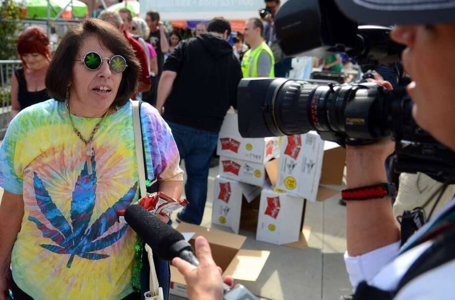 A woman is interview about the bags of Doritos affixed with a sticker that helps spell out rules for marijuana users during the second day of the annual festival Saturday, Aug. 17, 2013. This is the first year for the annual pro-pot rally since Washington State voters legalized recreational use of marijuana. (Sy Bean, seattlepi.com) Photo: SY BEAN, SEATTLEPI.COM