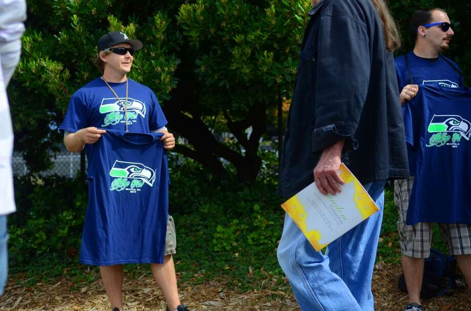 """Chron Dom"" sells homemade t-shirts with the logo of the Seahawks with a joint in its mouth during the second day of the annual Hempfest Saturday, Aug. 17, 2013. This is the first year for the annual pro-pot rally since Washington State voters legalized recreational use of marijuana. (Sy Bean, seattlepi.com) Photo: SY BEAN, SEATTLEPI.COM"