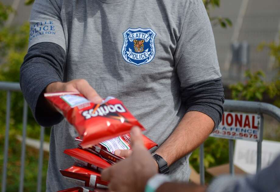 Detective Mark Jamieson hands out bags of Doritos affixed with a sticker that helps spell out rules for marijuana users during the second day of the annual festival Saturday, Aug. 17, 2013. This is the first year for the annual pro-pot rally since Washington State voters legalized recreational use of marijuana. (Sy Bean, seattlepi.com) Photo: SY BEAN, SEATTLEPI.COM