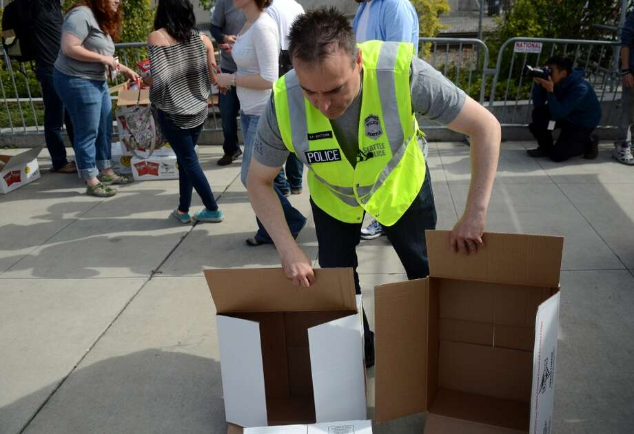 Seattle Police Sgt. Sean Whitcomb disposes of the boxes that held bags of Doritos affixed with a sticker that helps spell out rules for marijuana users during the second day of the annual festival Saturday, Aug. 17, 2013. This is the first year for the annual pro-pot rally since Washington State voters legalized recreational use of marijuana. (Sy Bean, seattlepi.com) Photo: SY BEAN, SEATTLEPI.COM