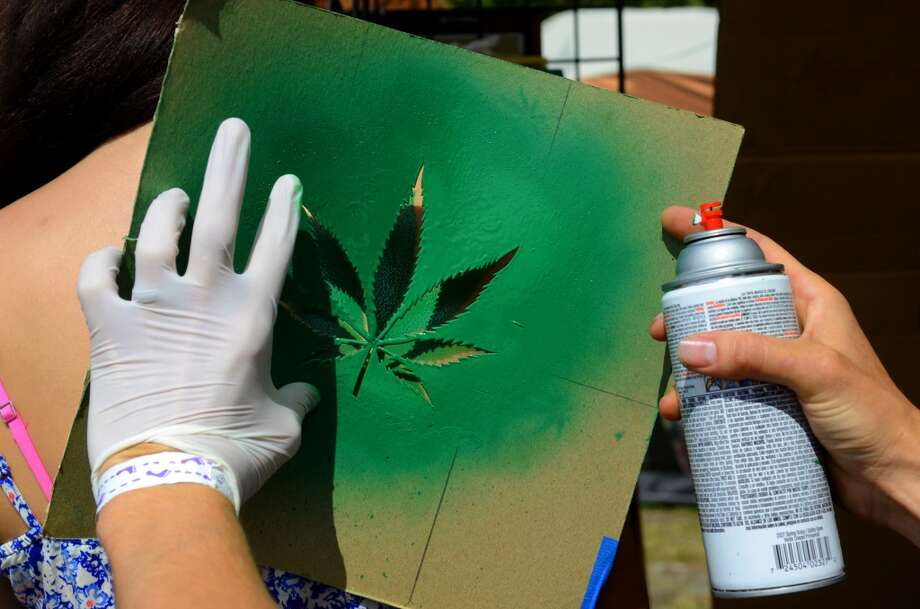 Artist Dave Ryan spray paints on a marijuana leaf on a festival attendee during the second day of the annual Hempfest Saturday, Aug. 17, 2013, at Myrtle Edwards Park in Seattle. This is the first year for the annual pro-pot rally since Washington State voters legalized recreational use of marijuana. (Sy Bean, seattlepi.com) Photo: SY BEAN, SEATTLEPI.COM