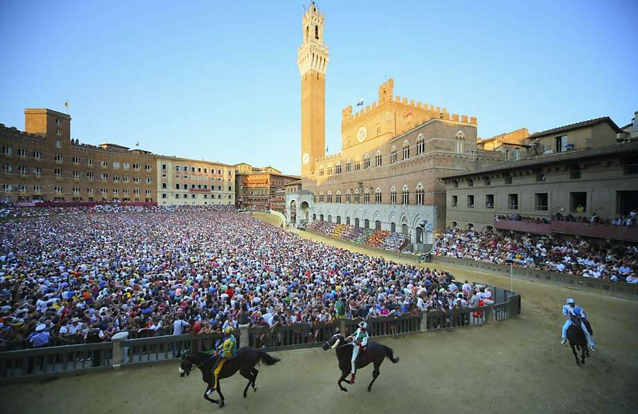 Riders take part in a practice race a day before the Palio di Siena horse race in Siena on August 15, 2013. The Palio di Siena (known locally simply as Il Palio), is a horse race held twice a year in the Tuscan city of Siena, in which jockeys ride bareback around a makeshift race course set up in the city's central square Photo: Fabio Muzzi, AFP/Getty Images