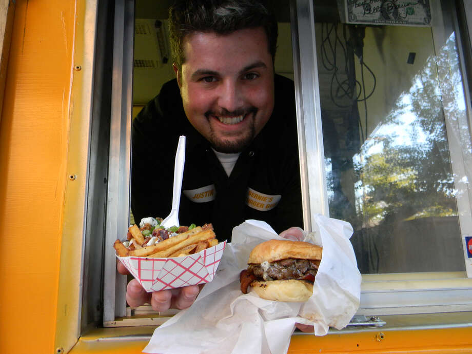 Justin Turner of Bernie's Burger Bus now has three school buses selling hand-crafted gourmet burgers and he will operate a booth at Houston Texans games in Reliant Stadium. Photo: Paul Galvani