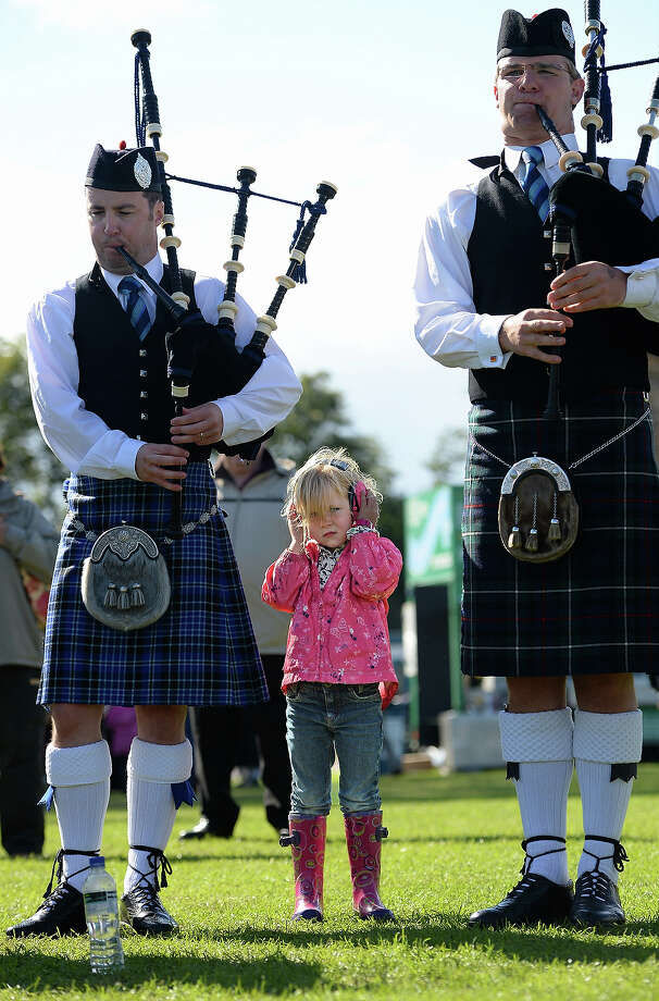 A young girl wears ear defenders as a pipe band takes part in 2013 World Pipe Band Championships at Glasgow Green on August 18, 2013 in Glasgow, Scotland. The annual World Pipe Band Championships has returned to Glasgow this weekend, with 225 pipe bands competing for the title. Photo: Jeff J Mitchell, Getty Images / 2013 Getty Images
