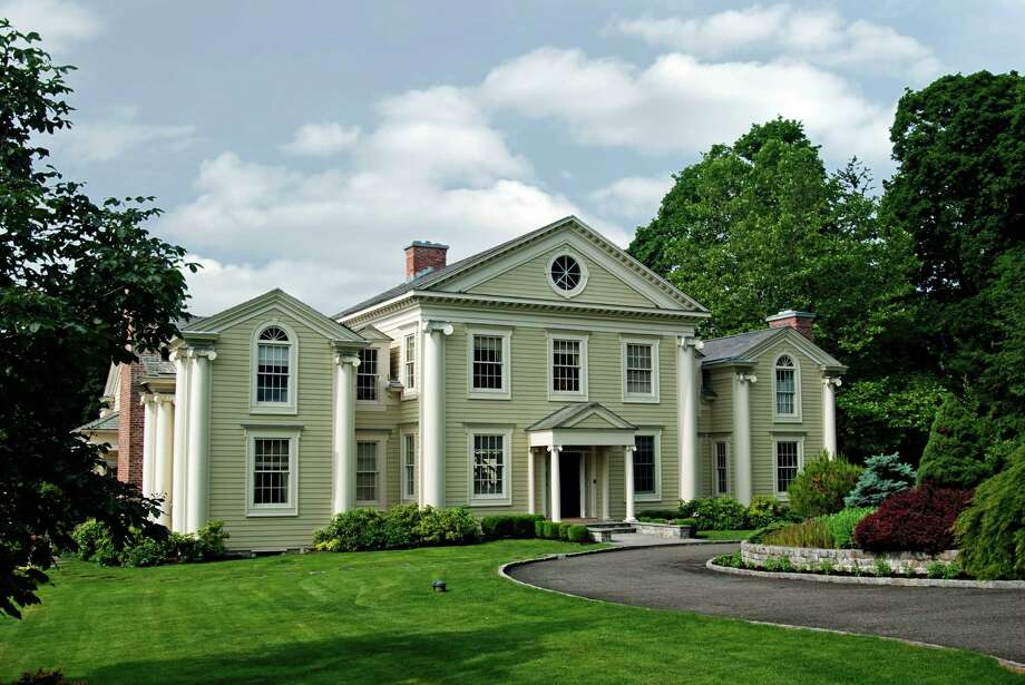 The Federal-style Colonial at 235 Brushy Ridge Road in New Canaan, on the market for $3.6 million, is surrounded by more than 4 acres of pristine property. Photo: Contributed