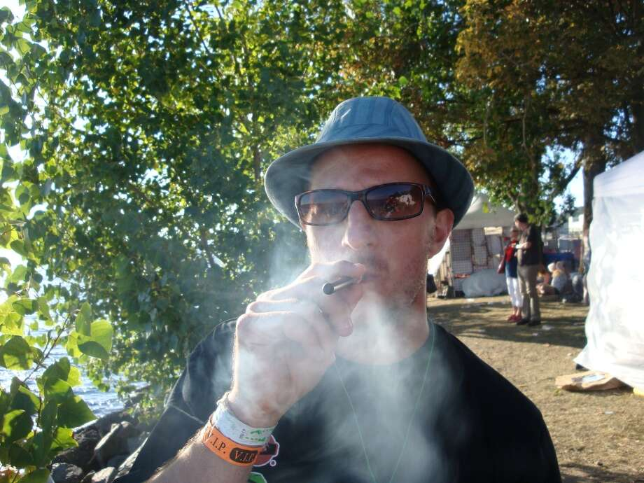 Being both discrete and super potent, hash oil vaporizer pens are quite popular these days. This Seattle Hempfest visitor demonstrates. Photo: Ben Livingston