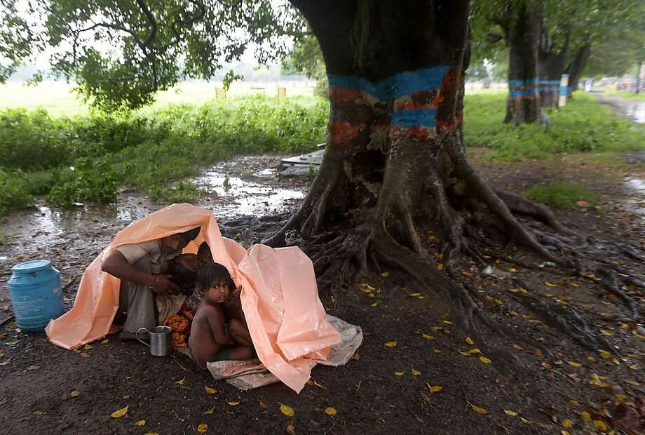 Shelter in a storm:An Indian migrant laborer and his children take cover from the monsoon rain on a   roadside in Kolkata. Photo: Dibyangshu Sarkar, AFP/Getty Images