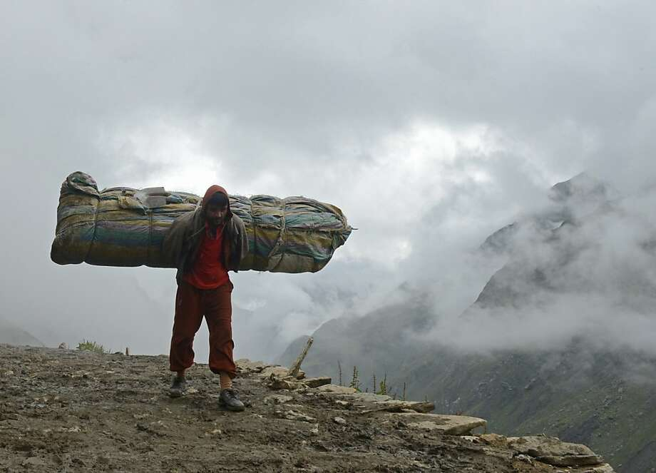 Caution, wide load:A Kashmiri Muslim carries belongings of Hindu pilgrims on a 