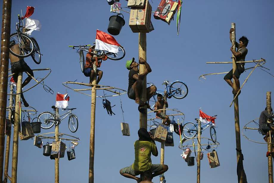 Oily risers: Contestants struggle to reach prizes perched atop greased poles during an Independence Day celebration at Jaya Ancol Dream Park in Jakarta. Photo: Dita Alangkara, Associated Press