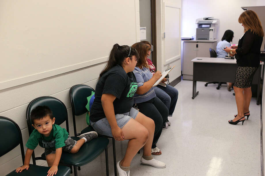 Two-year-old Noel Medina plays as his mother, Leticia Medina, 45, fills out an application Aug. 15 at Bexar County's first school-based health center. The family was at there to get vaccinations for Ashley Medina, 14, in shorts. Photo: Jerry Lara / San Antonio Express-News