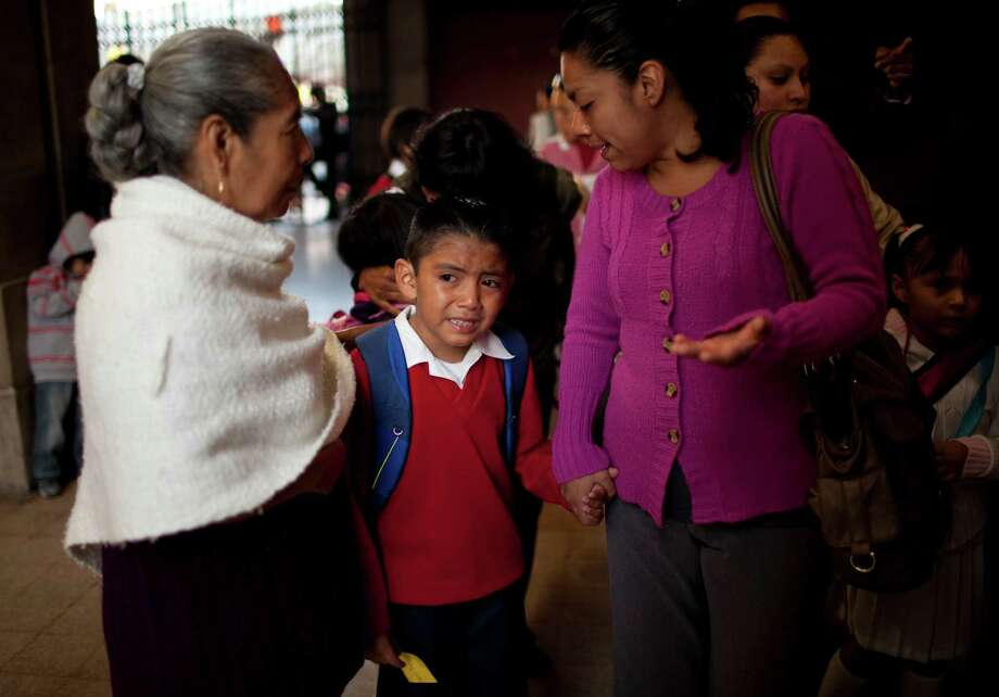 "Diego Angel is consoled by his mother Dulce Castro, right, and grandmother Margarita as he is escorted to the first day of classes in Mexico City, Monday, Aug. 19, 2013. Mexican children returned to classrooms Monday, and they were getting a quick lesson: Not just school kids make mistakes. Their brand new textbooks have the kinds of errors that they are supposed to be learning not to make: words written with a ""c'' instead of an ""s,"" too many commas, not enough accents and at least one city located in the wrong state. (AP Photo/Ivan Pierre Aguirre) Photo: Ivan Pierre Aguirre, STF / AP"