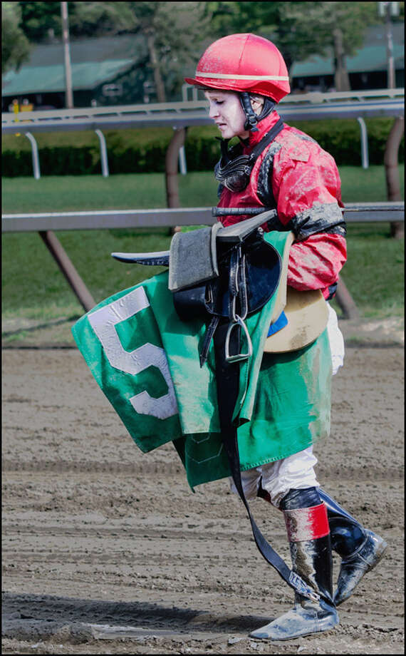 Taken on July 29, 2013, Rossie pulled up her horse right after the stretch turn due to a suspected injury.  She removed all of the tack and this is her leaving the track where she stopped racing. (Mike Mosher)