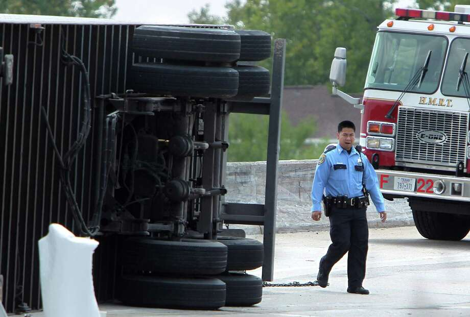 HPD officers work the scene of an accident where an overturned 18-wheeler carrying tile material is blocking I-10 eastbound on ramp to 59 North on Monday, Aug. 19, 2013, in Houston. Photo: Mayra Beltran, Houston Chronicle / © 2013 Houston Chronicle