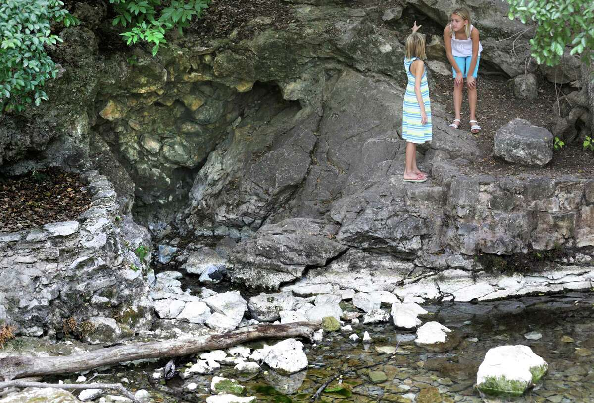 Emily Self, 11 (right), listens to sister Madison Self, 9, talk about the the springs in Landa Park. The girls' father, Greg Self, took them to the springs for a lesson on how important water is and how the current drought affects the springs.