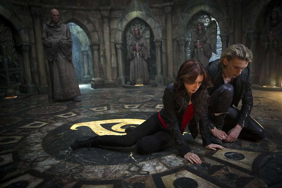Clary (Lilly Collins) and Jace (Jamie Campbell Bower) look at what Clary wrote while the Brothers were trying to unlock her mind in Screen Gems' fantasy-action THE MORTAL INSTRUMENTS: CITY OF BONES.