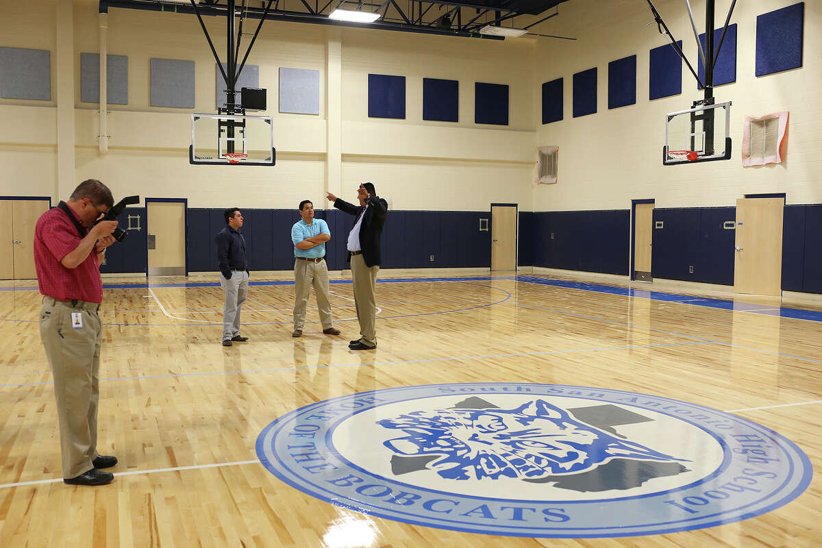 South San Antonio Independent School District public information officer Ed Suarez photographs the logo on the floor of the girl's gym in the new South San High School, Monday, Aug. 19, 2013. The school is part of a $58 million bond and will open with the coming school year.