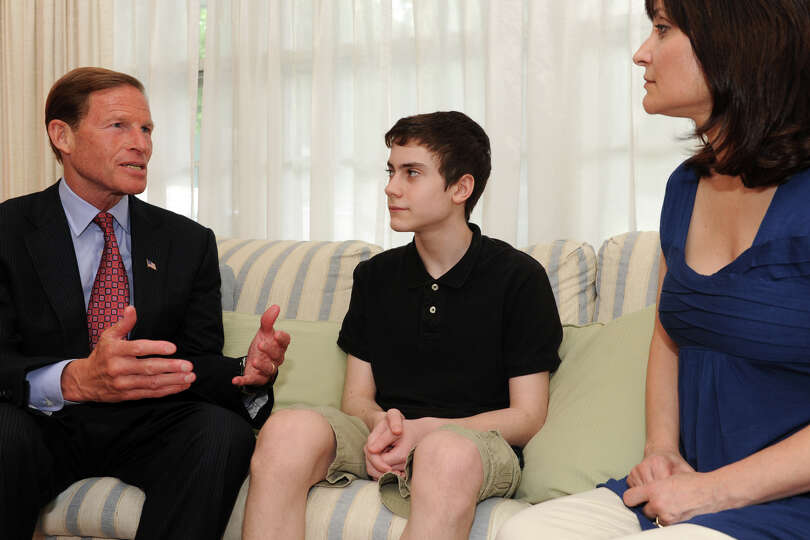 Sen. Richard Blumenthal speaks with Max Wheeler, 13, and his mother, Maria, in their Trumbull, Conn.