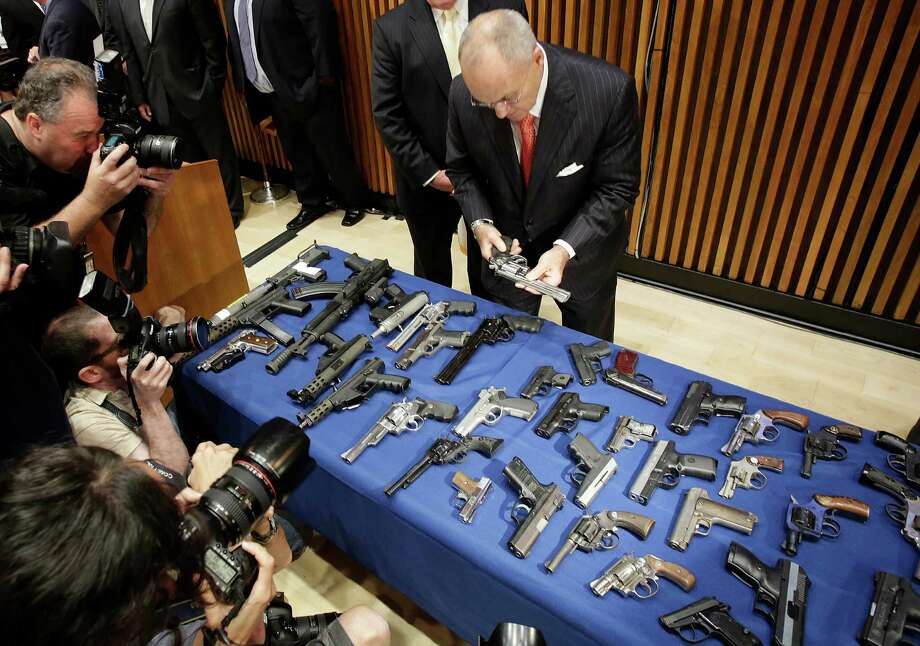 New York Police Commissioner Raymond Kelly examines some of the weapons seized as part of gun smuggling between the Carolinas and New York. Photo: Mark Lennihan, STF / AP