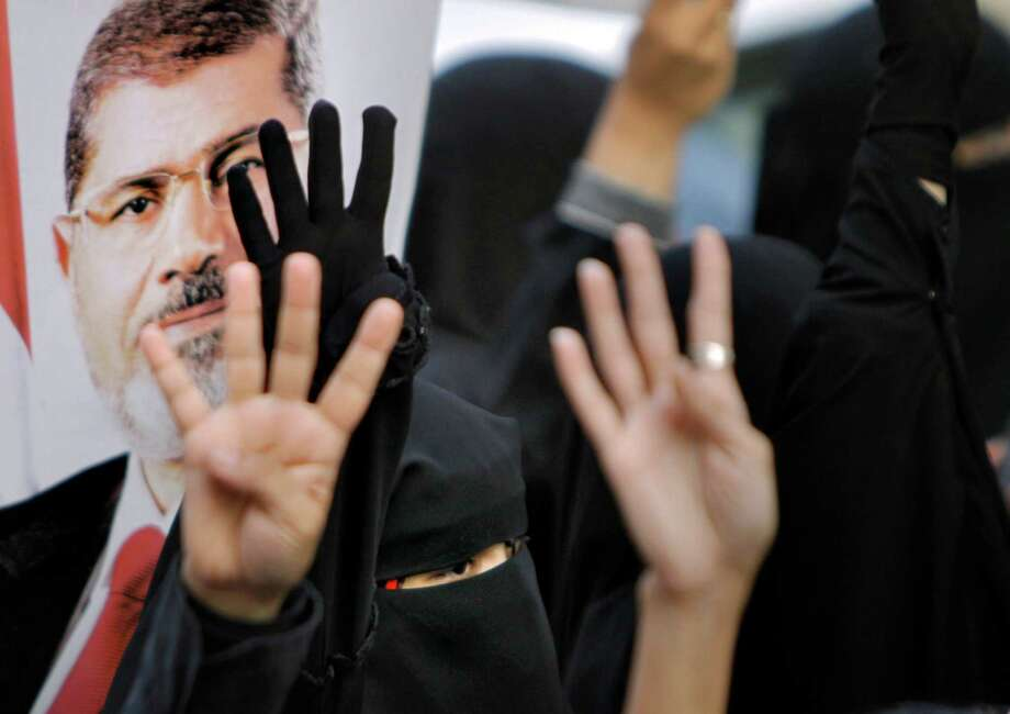 Supporters of ousted Egyptian President Mohammed Morsi raise four fingers, a sign protesters say symbolizes the Rabaah al-Adawiya mosque in Cairo that was cleared last week by security forces, during a Monday march in Cairo. Photo: Amr Nabil, STF / AP