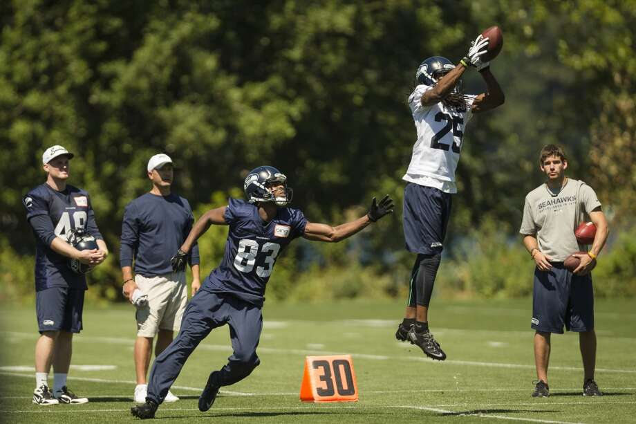 Richard Sherman leaps to make a catch in front of Stephen Williams at the opening day of Seahawks training camp. Photo: JORDAN STEAD, SEATTLEPI.COM