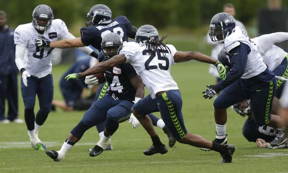 Spencer Ware runs the ball as cornerback Richard Sherman and linebacker Allen Bradford close in. Photo: Ted S. Warren, AP