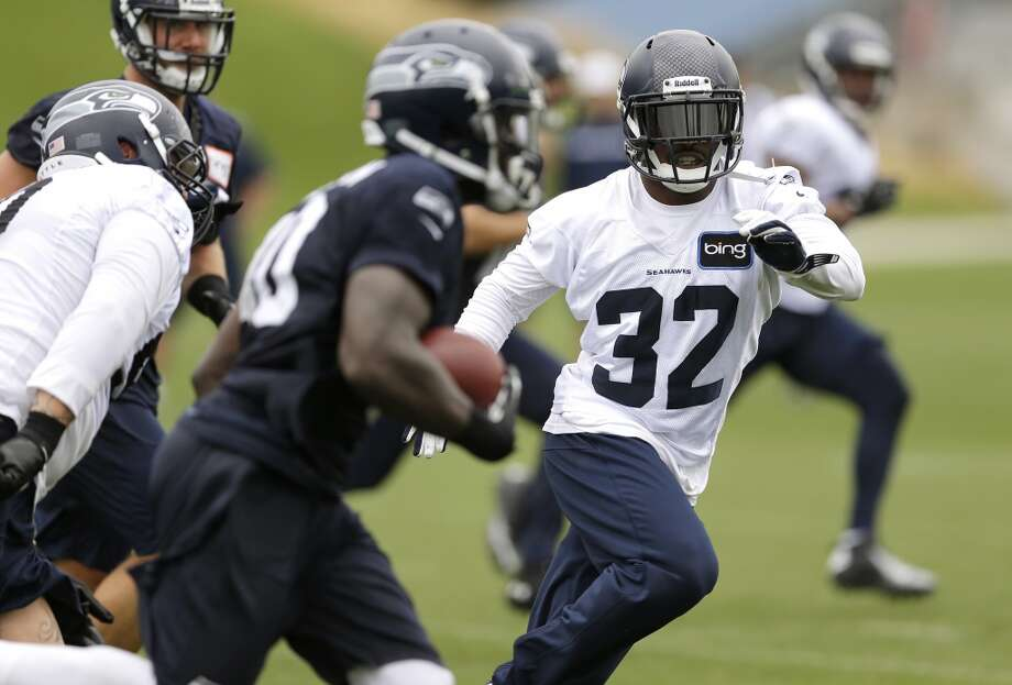 Jeron Johnson moves in on running back Derrick Coleman during Seahawks training camp. Photo: Ted S. Warren, AP