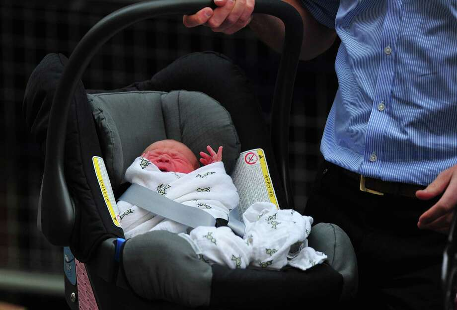 Britain's Prince William, Duke of Cambridge, carries his new-born son Prince George of Cambridge in a car seat after presenting the new-born to the world's media outside the Lindo Wing of St Mary's Hospital in London on July 23. Photo: CARL COURT, AFP/Getty Images / AFP ImageForum