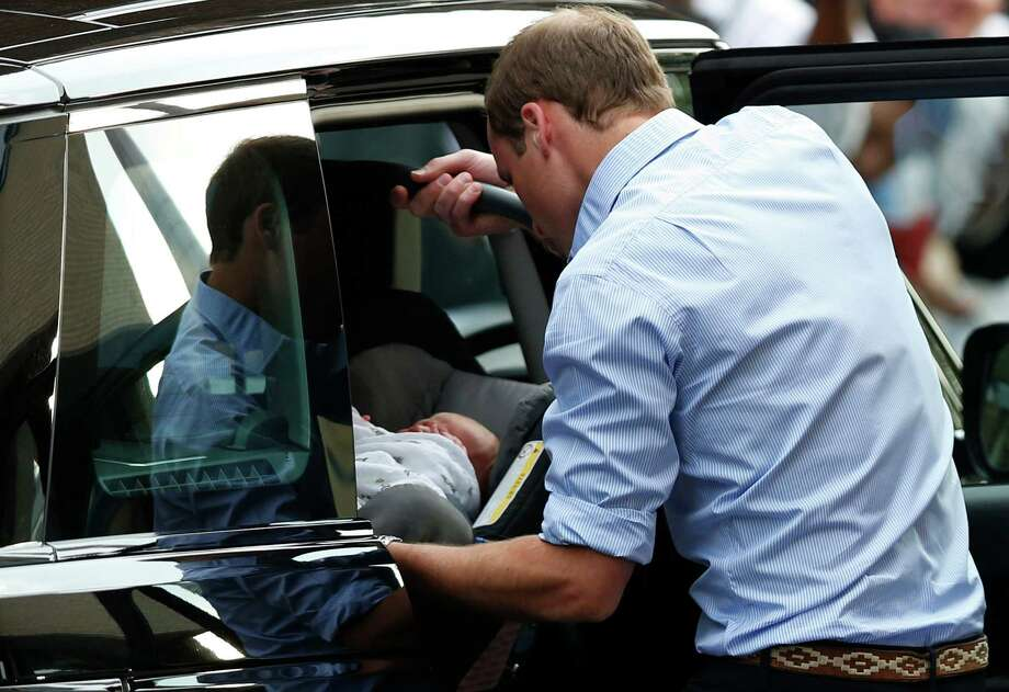 Britain's Prince William places carefully the Prince George of Cambridge into a car, Tuesday July 23, 2013, as they leave St. Mary's Hospital exclusive Lindo Wing in London where the Duchess gave birth on Monday July 22.  Photo: Sang Tan, Associated Press / AP