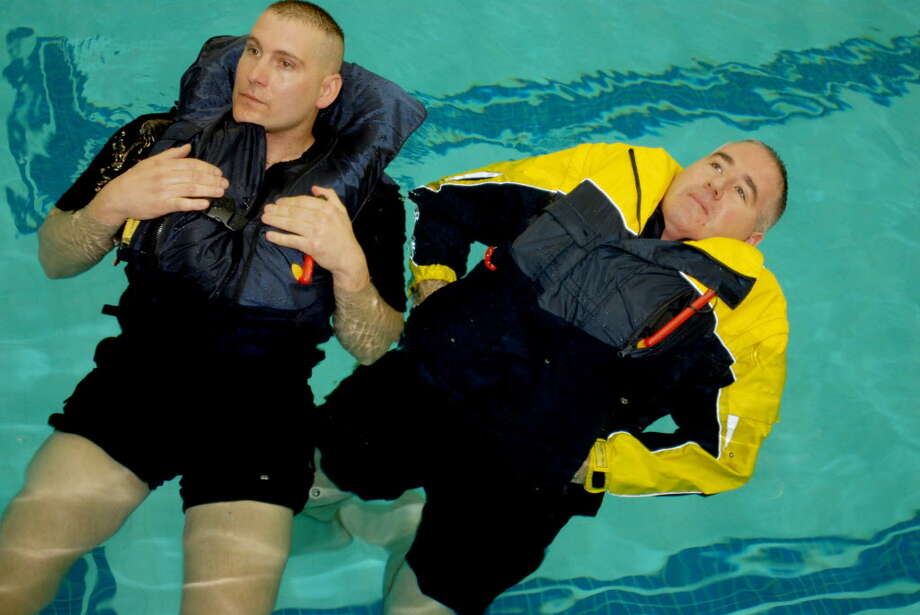 Rensselaer County Sheriff deputies Mark Geracitano, left, and Corey Film demonstrate Float-Tech flotation jackets in the pool of the East Greenbush YMCA in this 2008 archive photo. (Times Union archive) Photo: LMF / ALBANY TIMES UNION
