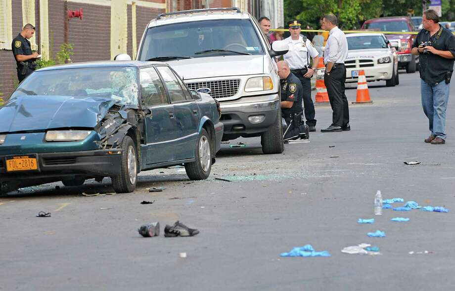 Police investigate a scene where a fight broke out and several people and the blue car on left were driven over by a person driving the white SUV on Elk St. Monday, Aug. 19, 2013 in Albany, N.Y. (Lori Van Buren / Times Union) Photo: Lori Van Buren