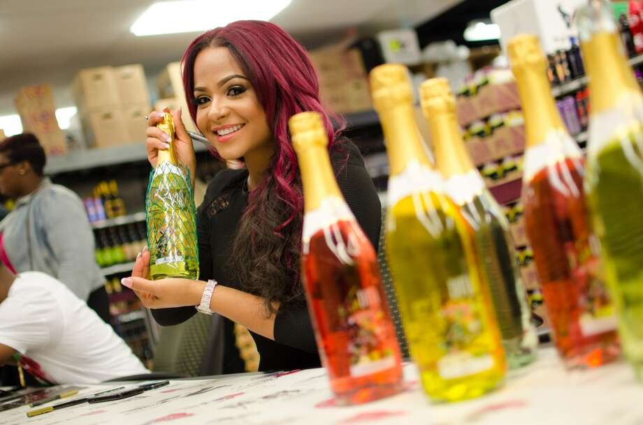 Christina Milian holding a bottle of peach mocato during her autograph session for Viva Diva Moscato and Wine at Spec's in Midtown Houston on Saturday. Photo: J.vince Photography, For The Chronicle