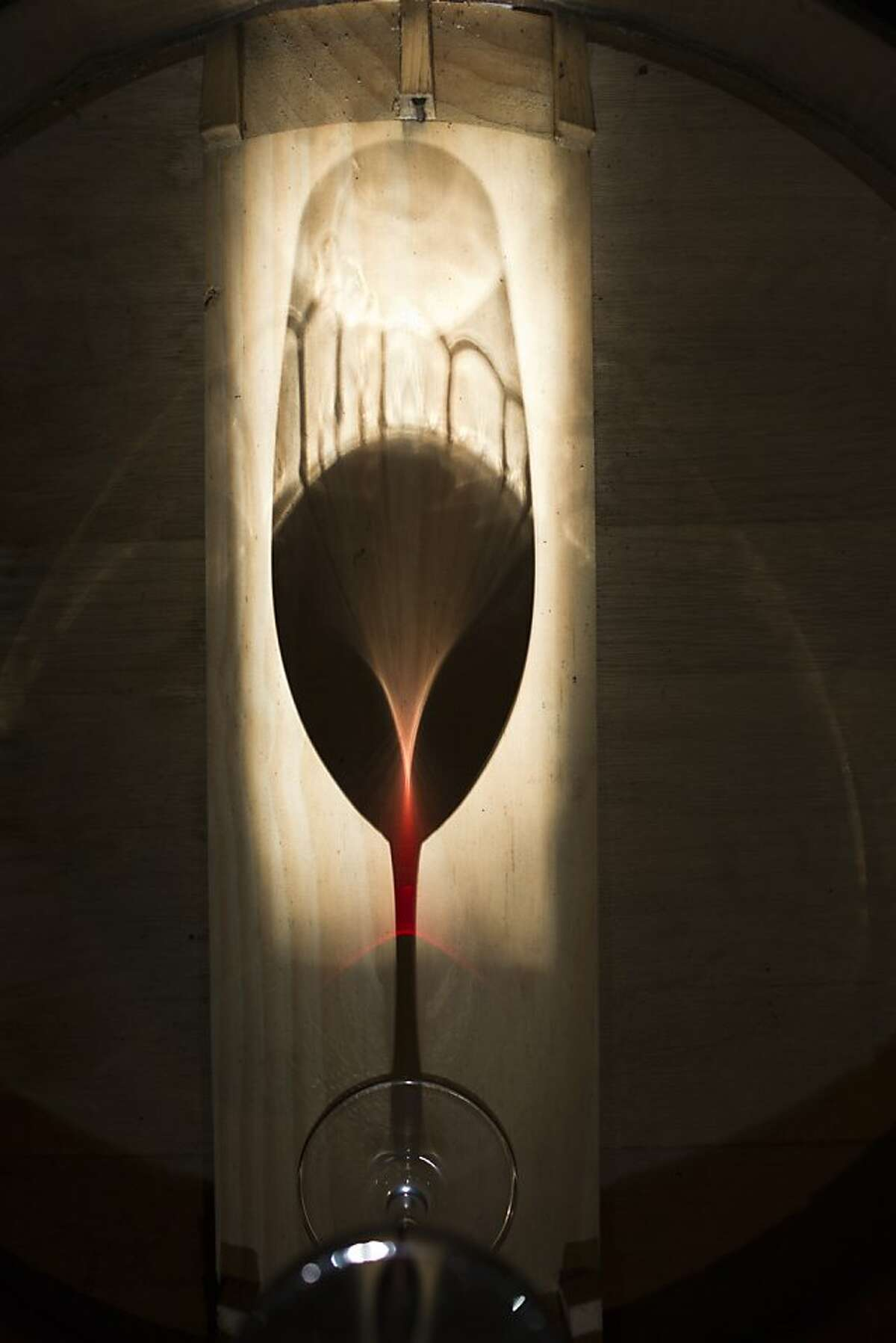 Light shines through a glass of Farella syrah at Farella Vineyards in Coombsville, Calif., Thursday, August 15, 2013.