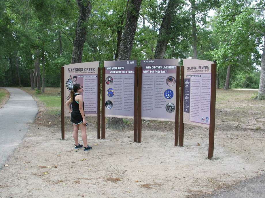 A jogger pauses during a morning run in Meyer Park to read new interpretive signs about archeological finds along Cypress Creek. The second and final phase of a channel restoration project on Cypress Creek has been completed.