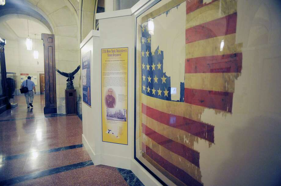 A view of the flag of the 27th New York Volunteers at a new exhibit of Civil War battle flags,  entitled 1863: Loyal Till Death, on display on the first floor at the State Capitol, seen here on Monday, Aug. 19, 2013 in Albany, NY.  The flag was initially presented to Company I by Elizabeth Church in Belvidere, New York, in April 1861, and later adopted by the regiment as its national color.  The flag was carried in battle for two years and many times struck by enemy fire. (Paul Buckowski / Times Union) Photo: Paul Buckowski / 00023555A