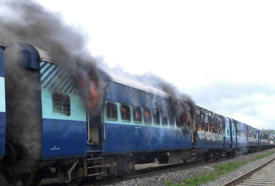 Coaches of the Rajya Rani Express train burn after a mob set it on fire as it ran over a group of Hindu pilgrims at a crowded station in Dhamara Ghat, Bihar state, India, Monday, Aug.19, 2013. At least 37 people were killed. (AP Photo) Photo: STR / AP